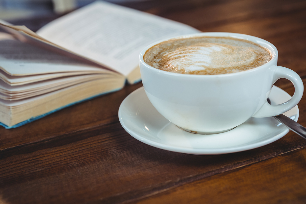 Close-up of cappuccino and book on table in cafeteria