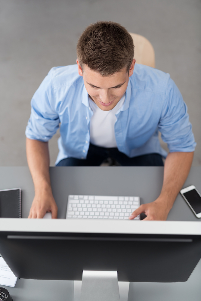 High Angle View of a Young Office Man Sitting at his Table and Working on his Desktop Computer.